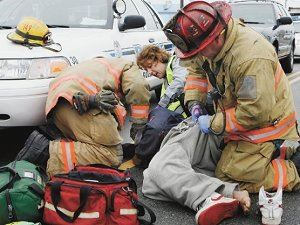 EMS workers respond to a car accident and help an injured victim.