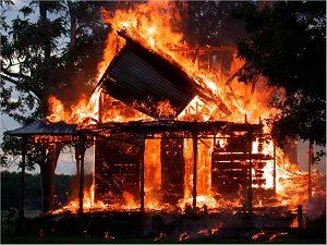 A house in the woods is completely engulfed in flames.