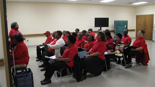 All dressed in matching red shirts, the Songbirds choir rehearse a song.
