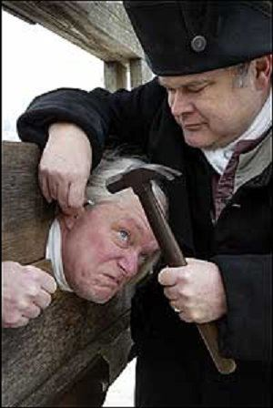 A sheriff in the English colonies places a man in the stocks.
