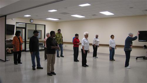 Members of the Songbirds stand up and rehearse.