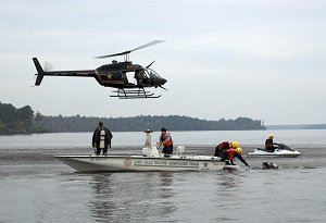 A helicopter hovers over 2 search and rescue boats.